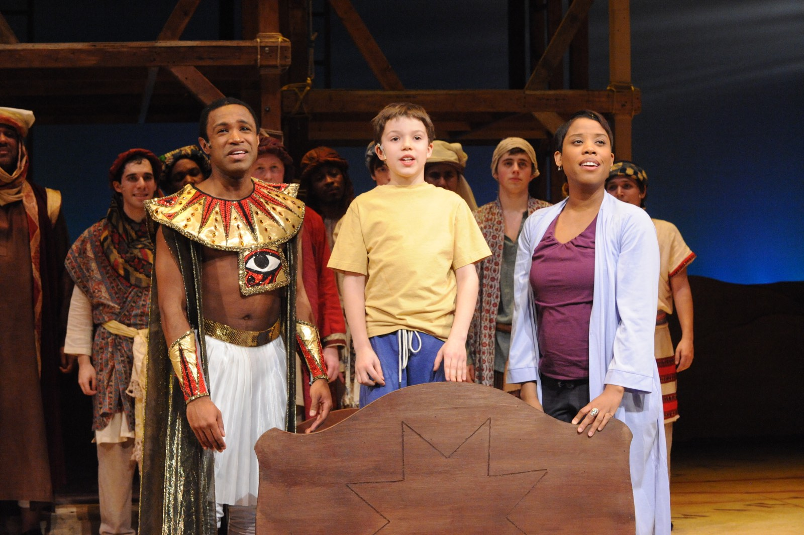 JOSEPH AND THE AMAZING TECHNICOLOR DREAMCOAT - Alan Wiggins as Joseph, Sean Silvia as the Boy, and Eleasha Gamble* as the Narrator in front of the ensemble<br>Set design by Eugenia Furneaux, Lighting by Dan Covey, Costumes by Ivania Stack - photo by Stan Barouh